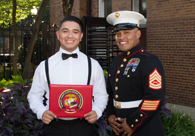 a graduate smiling with a marine